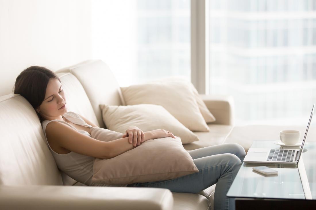 sleepy young woman sitting on settee