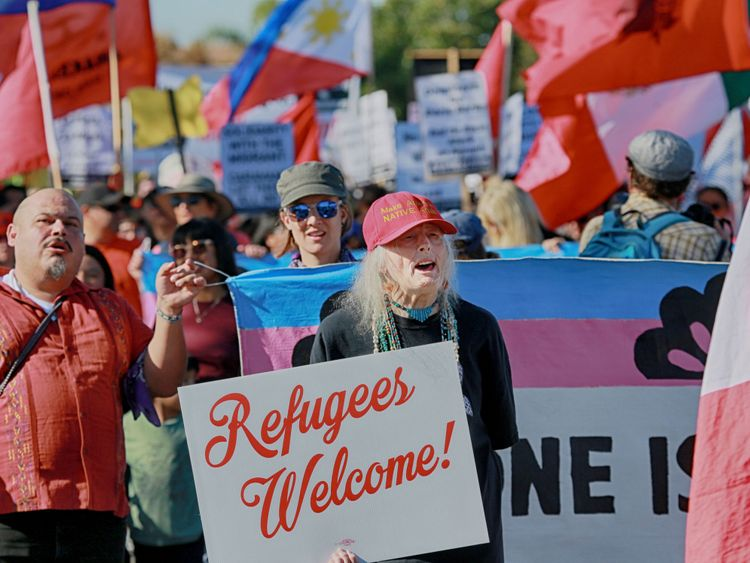 Protesters march along the US-Mexico border to show solidarity with the migrant caravan