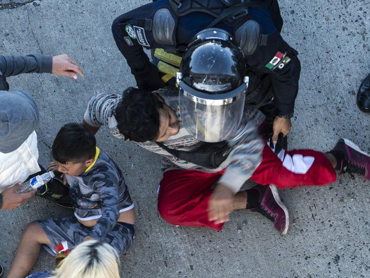 Mexican police stop migrants as they reach the El Chaparral border crossing