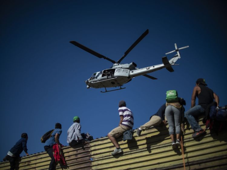 A US military helicopter hovers over a group of migrants as they blimb the border fence between Mexico and the US
