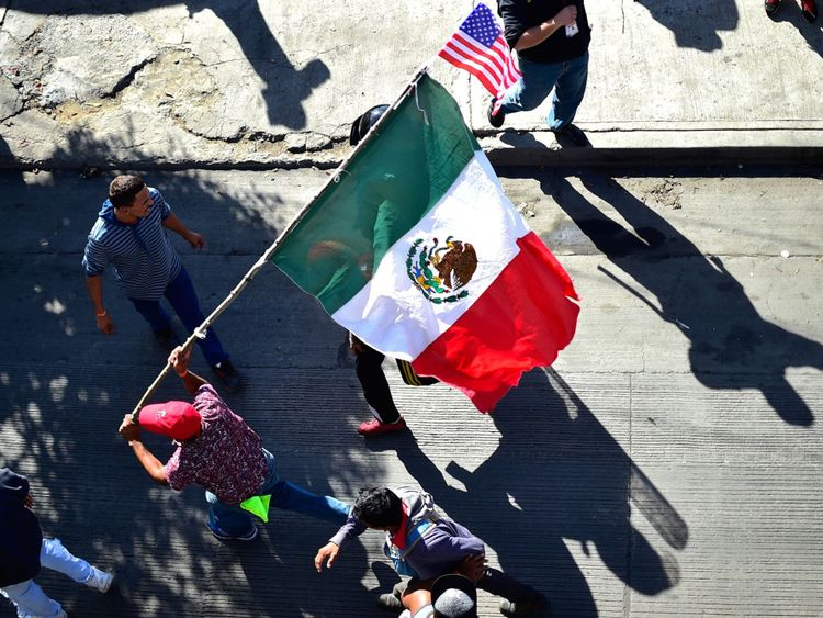 Migrants carry a Mexican and a US flag as they try to get to El Chaparral border crossing