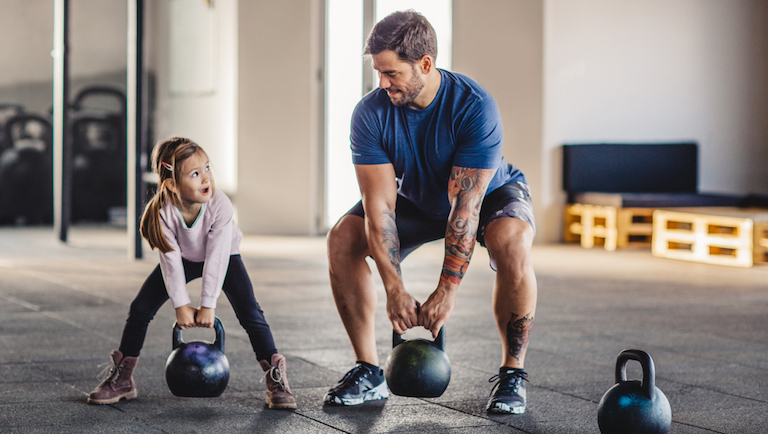 Father doing his training with kettlebells in gym while his little daughter supporting him.