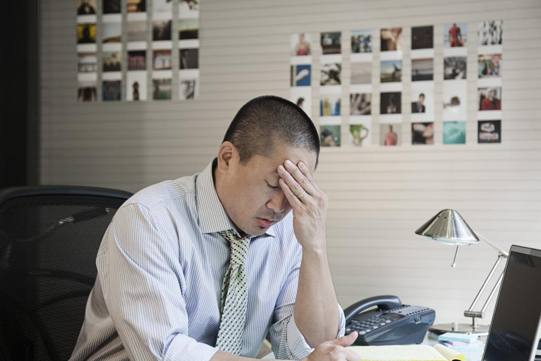 Stressed man at work holding head