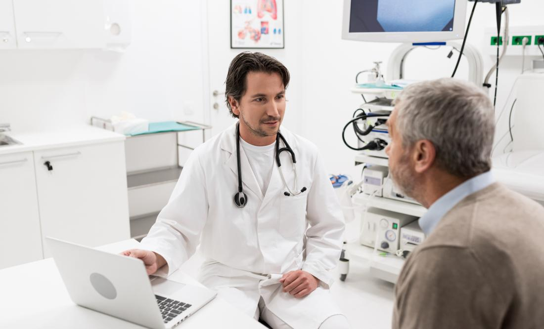 senior man speaking to young male doctor