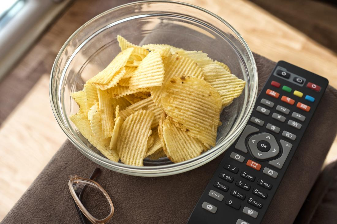 Chips or crisps in bowl next to tv remote