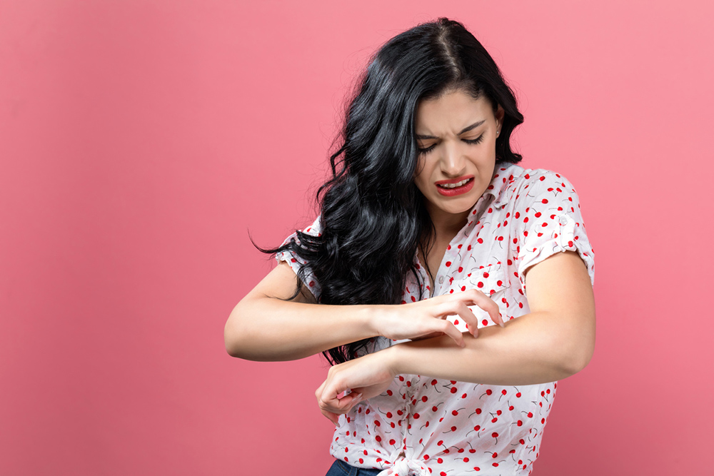4-ways-stress-is-showing-on-your-skin-and-exactly-how-to-cope-girl-scratching-arm.jpg
