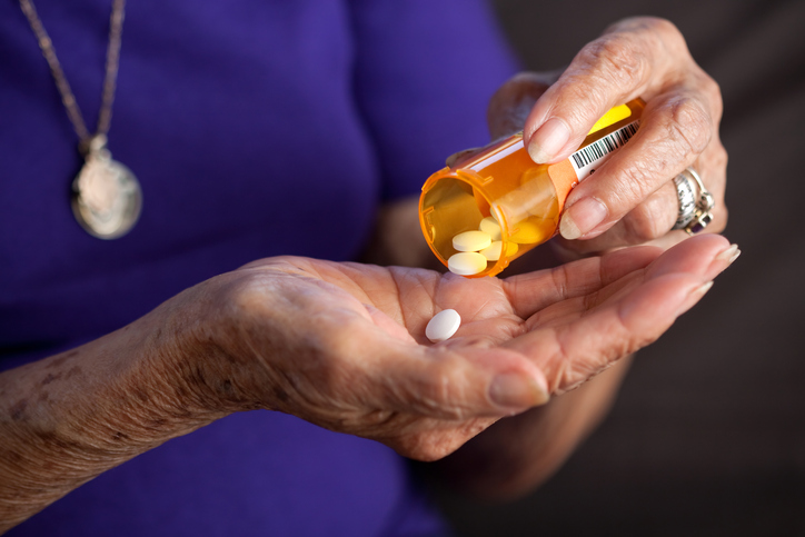 Older woman putting medicine from pill bottle into her hand